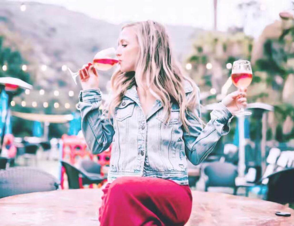 Ragazza che beve da due bicchieri di vino