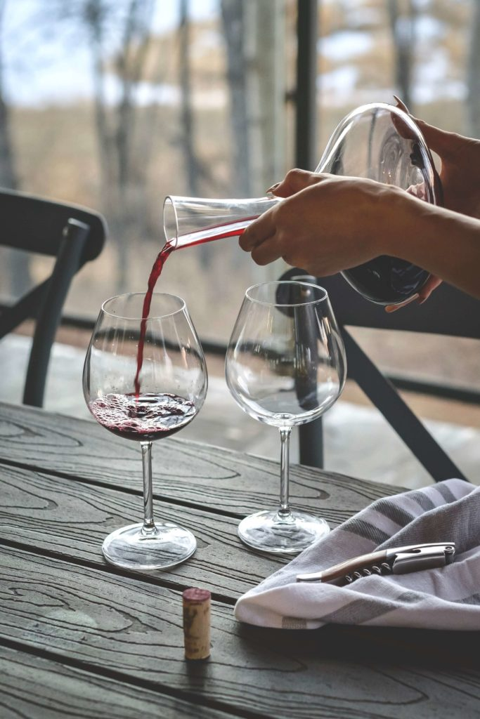 mani che versano del vino nei bicchieri